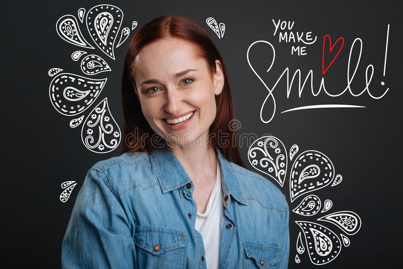 Zrelaksowana kobieta patrzeje szczęśliwy i uśmiechnięty podczas gdy być samotny zdjęcie stock