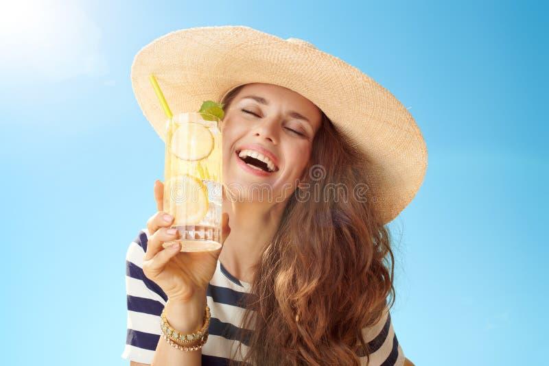 Zrelaksowana kobieta przeciw niebieskiemu niebu cieszy się odświeżającego koktajl zdjęcia stock