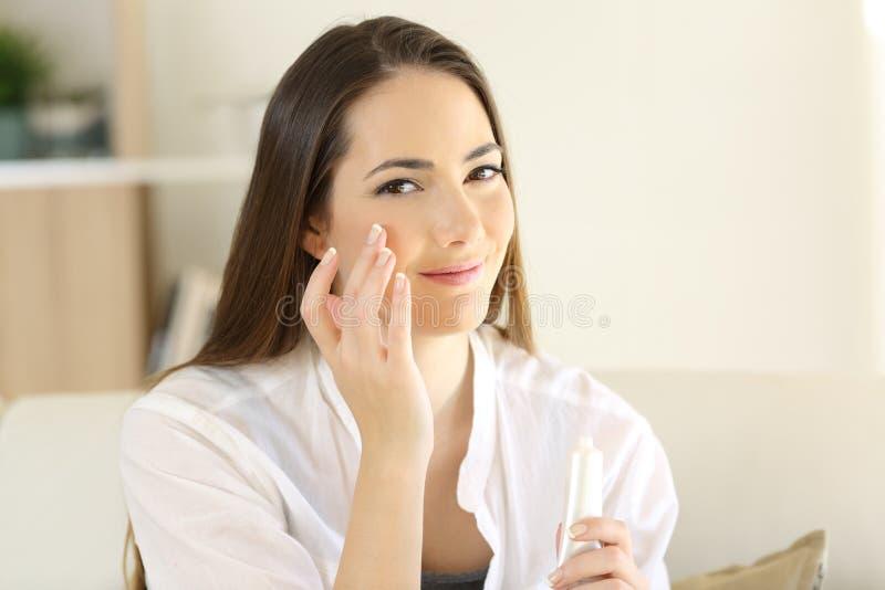 Zrelaksowana kobieta stosuje moisturizer śmietankę w policzku zdjęcia stock