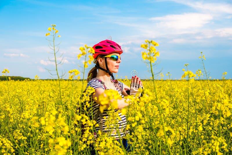 Zrelaksowana kobieta z czerwonymi rower wycinanki, hełma rękawiczkami robi joga pozie z rękami i zdjęcia royalty free