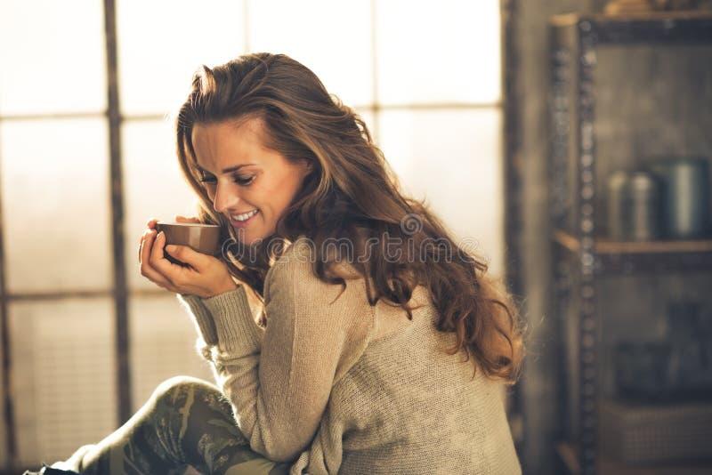 Zrelaksowana kobieta z filiżanką kawy w loft mieszkaniu fotografia royalty free