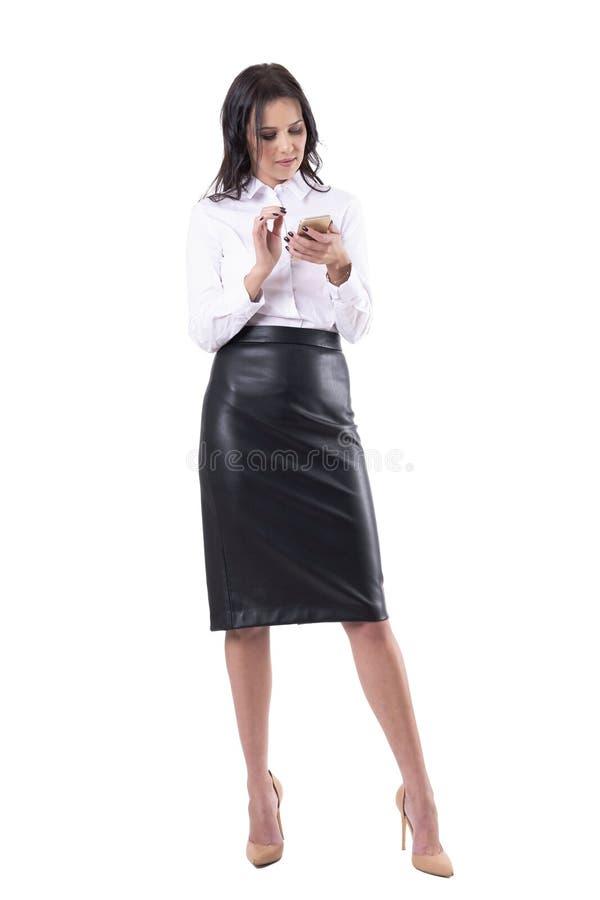 Zrelaksowana młoda biznesowa kobieta patrzeje telefon wyszukuje internet lub surfuje zdjęcie stock