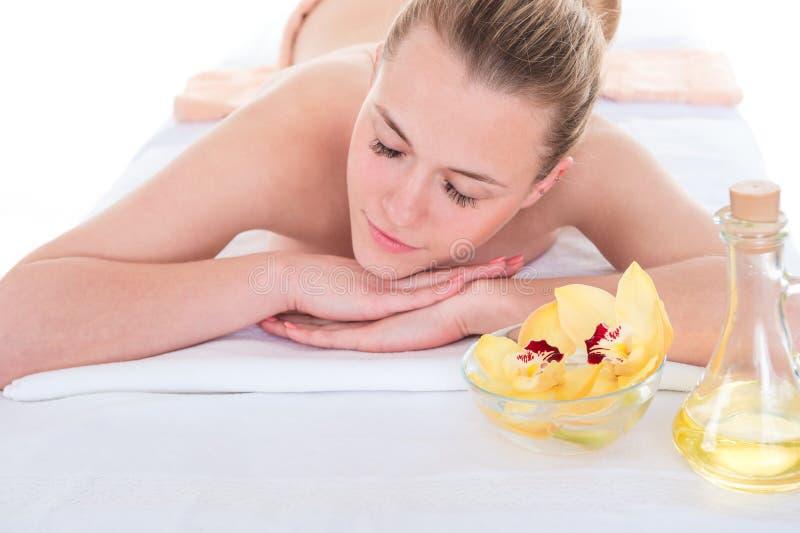 Zrelaksowana młoda kobieta i odzyskiwanie na masażu w zdroju fotografia stock