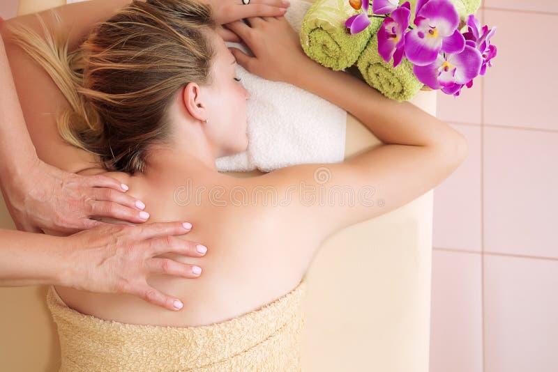 Zrelaksowana młoda kobieta na masażu stołu piękna odbiorczym traktowaniu przy dnia zdrojem zdjęcie stock
