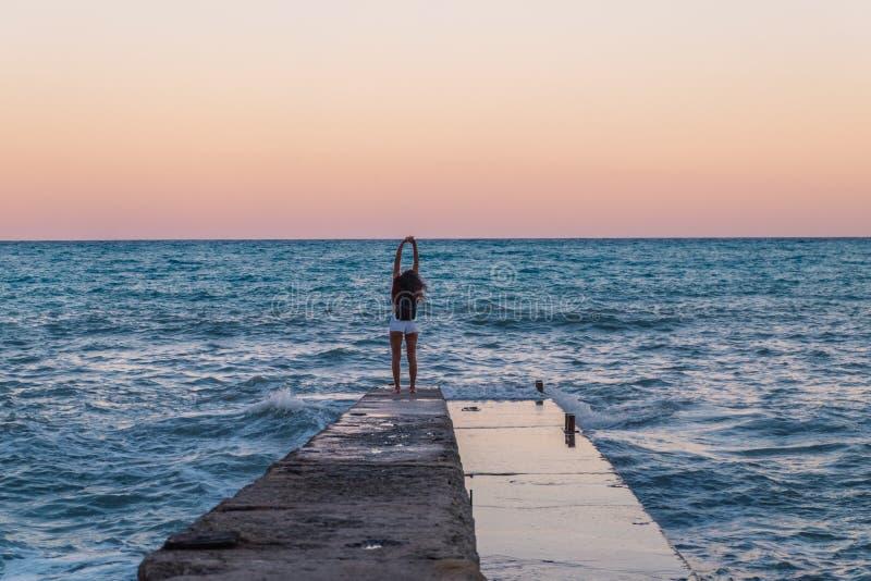 Zrelaksowana młoda kobieta na molu na tle morze obraz stock