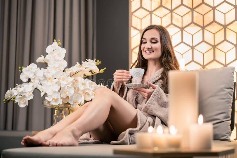 Zrelaksowana młoda kobieta pije ziołowej herbaty przed zdroju traktowaniem obraz royalty free