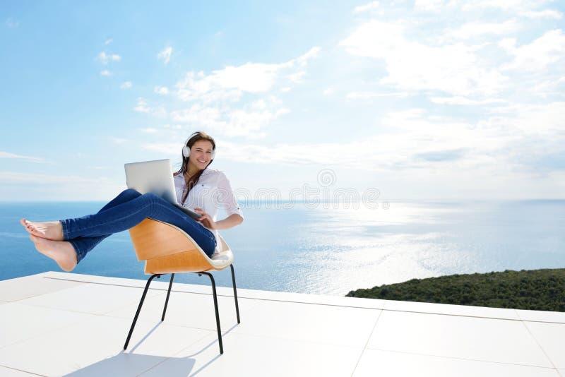Zrelaksowana młoda kobieta pracuje na laptopie w domu fotografia royalty free