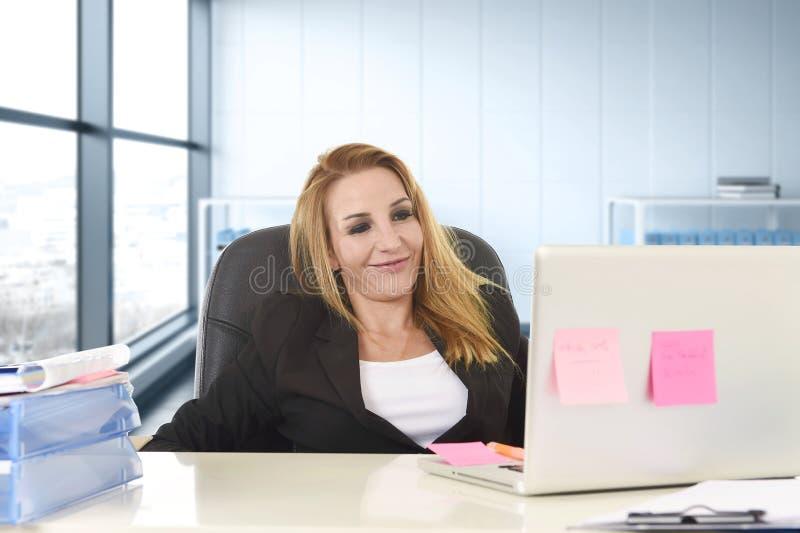 Zrelaksowana 40s kobieta z blondynu uśmiechniętym ufnym obsiadaniem na biurowym krześle pracuje przy laptopem obraz royalty free