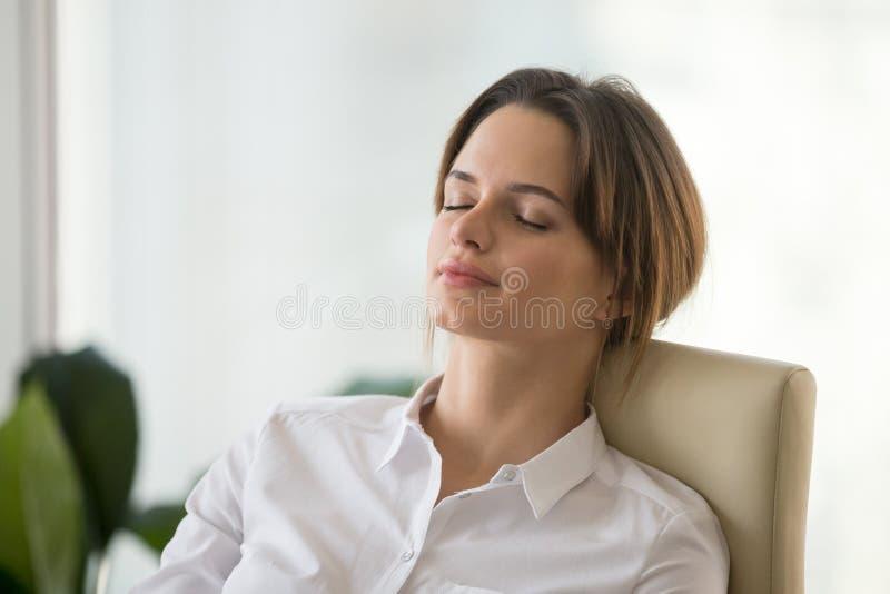 Zrelaksowana spokojna pamiętająca kobieta odpoczywa na wygodnym biurowym krześle zdjęcia royalty free