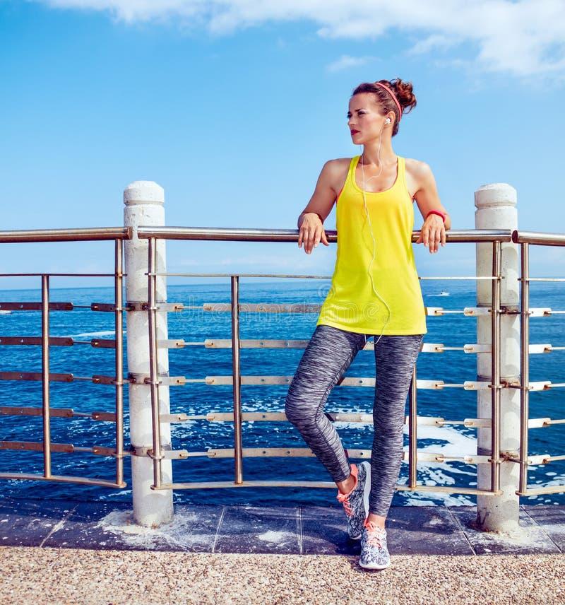 Zrelaksowana sprawności fizycznej kobieta patrzeje w odległość przy bulwarem fotografia stock