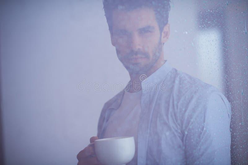 Zrelaksowanego młodego człowieka napoju pierwszy ranku withh kawowy deszcz opuszcza dalej zdjęcia stock