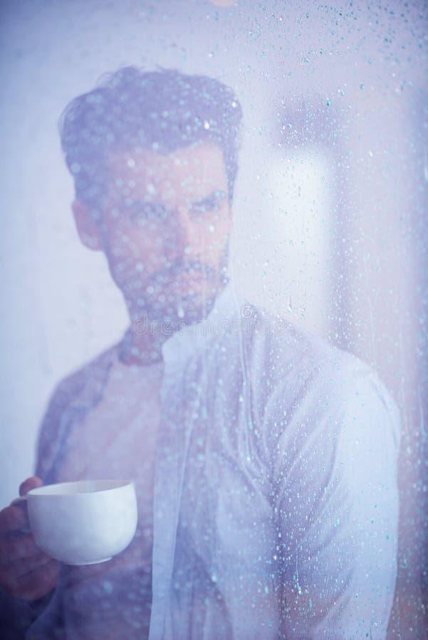 Zrelaksowanego młodego człowieka napoju pierwszy ranku withh kawowy deszcz opuszcza dalej obraz stock