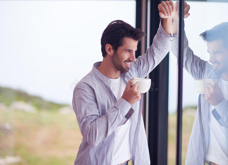 Zrelaksowanego młodego człowieka napoju pierwszy ranku withh kawowy deszcz opuszcza dalej fotografia stock