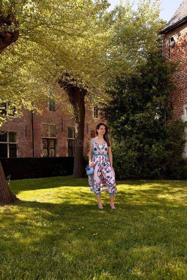 Zrelaksowanej kobiety trawy trwanie drzewo, Groot Begijnhof, Leuven, Belgia obrazy stock