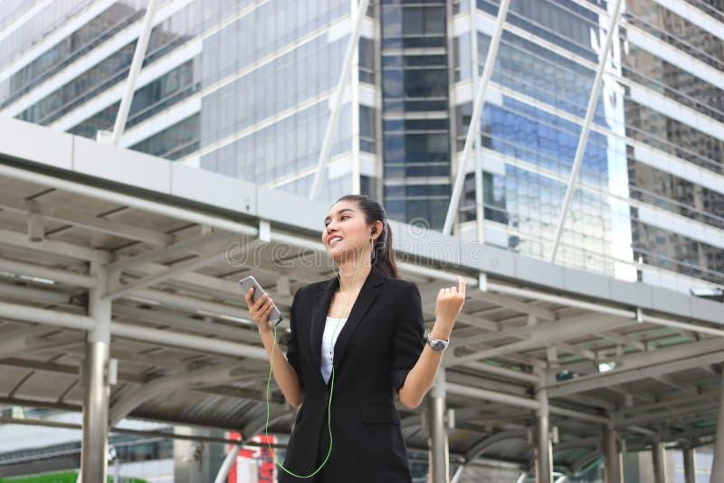 Zrelaksowanej młodej Azjatyckiej kobiety słuchająca muzyka z mobilnym mądrze telefonem w miastowym mieście obrazy royalty free