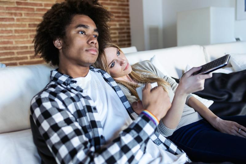 Zrelaksowani potomstwo pary odmieniania kanały z pilotem do tv podczas gdy oglądający TV na kanapie w domu obrazy stock