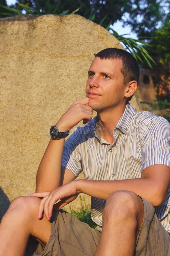 Zrelaksowany atrakcyjny uśmiechnięty mężczyzna siedzi w koszula, skrótach i godzinach, blisko ampuła kamienia zdjęcia stock