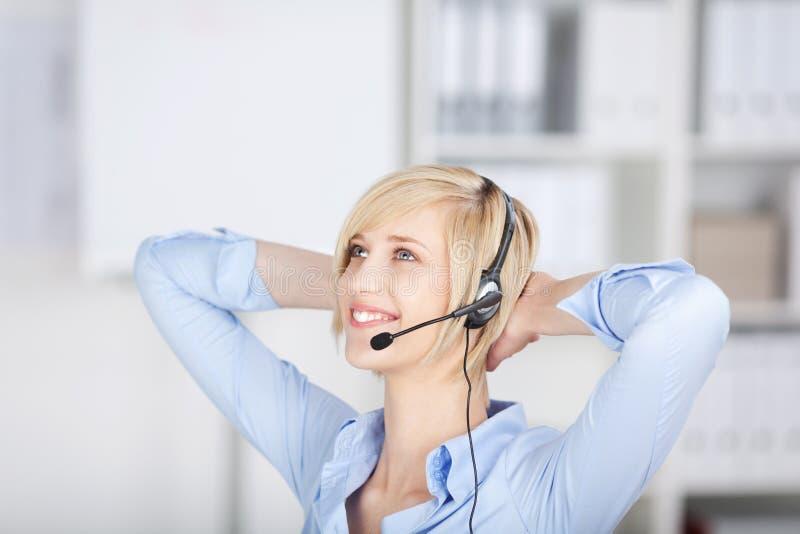 Zrelaksowany bizneswoman jest ubranym słuchawki obrazy royalty free