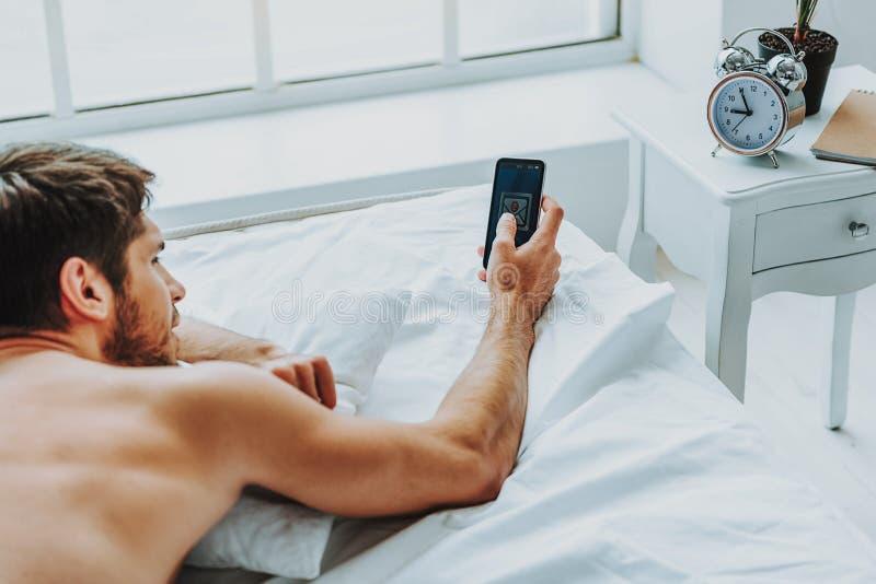 Zrelaksowany facet sprawdza telefon komórkowego w ranku zdjęcie stock