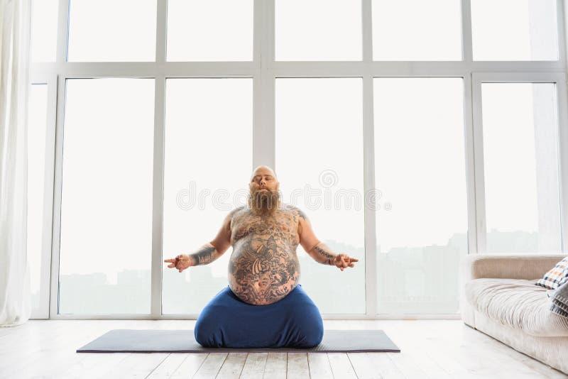 Zrelaksowany gęsty facet medytuje w domu zdjęcie stock
