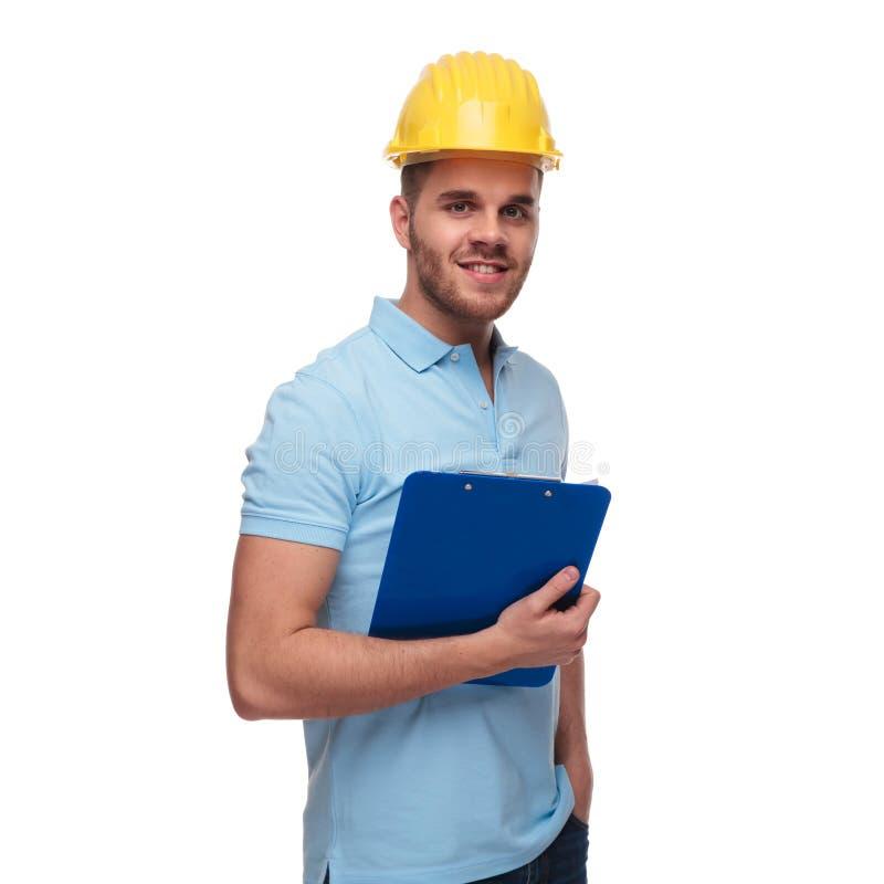 Zrelaksowany inżynier jest ubranym błękitną polo koszula trzyma kieszenie zdjęcie stock