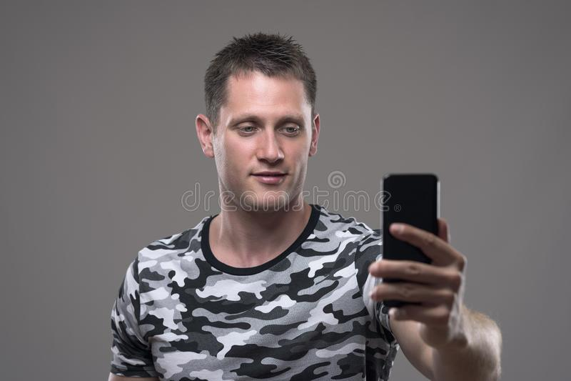 Zrelaksowany młody dorosłej samiec mienia telefon komórkowy, brać selfie i fotografie lub zdjęcie royalty free