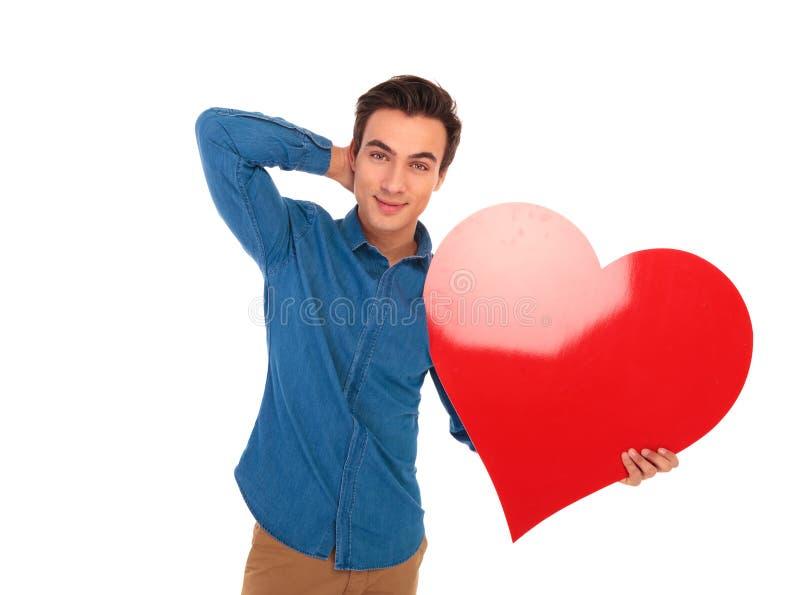 Zrelaksowany mężczyzna trzyma dużego czerwonego serce z ręką za szyją zdjęcia stock