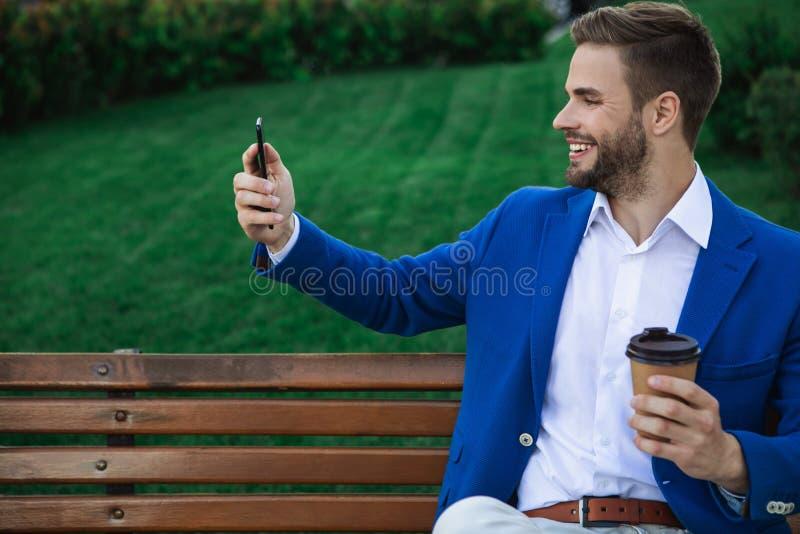 Zrelaksowany mężczyzna używa telefon komórkowego w naturze obraz stock