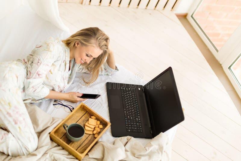 Zrelaksowany młodej kobiety wysylanie sms podczas gdy używać laptop w łóżku w domu fotografia royalty free
