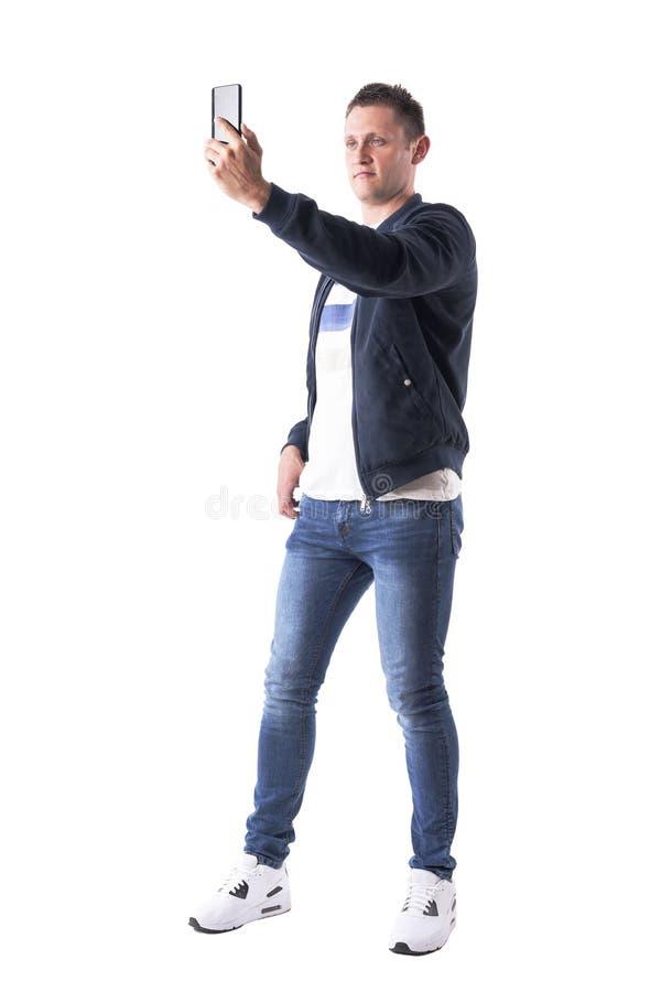 Zrelaksowany młody dorosły przypadkowy mężczyzna bierze selfie fotografie z mądrze telefonem pojęcia leżanki target1632_0_ styl ż zdjęcia royalty free