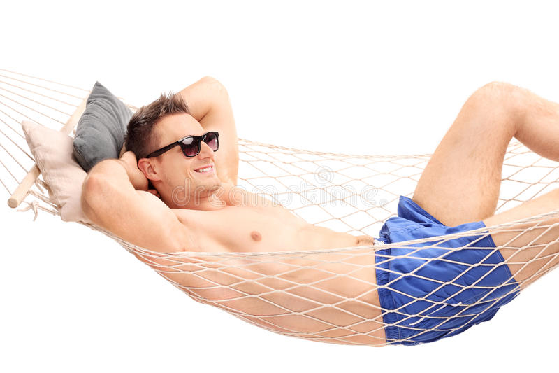 Zrelaksowany młody faceta lying on the beach w hamaku obraz stock
