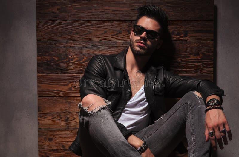 Zrelaksowany moda mężczyzna w okularach przeciwsłonecznych i skórzanej kurtce siedzi zdjęcia royalty free