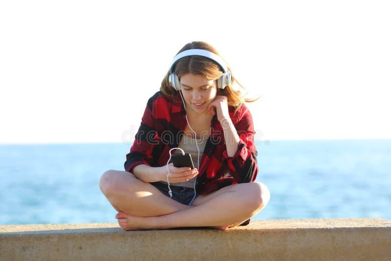 Zrelaksowany nastoletni s?ucha muzyka na pla?y obrazy royalty free