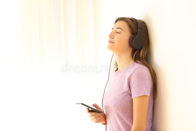Zrelaksowany nastoletni słuchanie muzyka na opierać ścianę fotografia royalty free