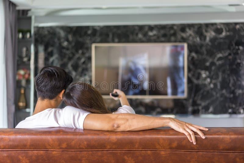 Zrelaksowany potomstw pary dopatrywanie tv w domu fotografia royalty free
