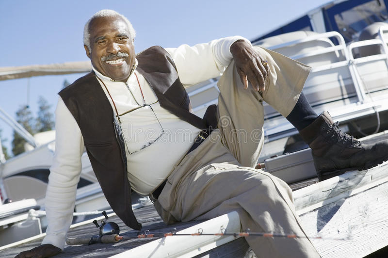 Zrelaksowany Starszego mężczyzna obsiadanie Na molu zdjęcie stock