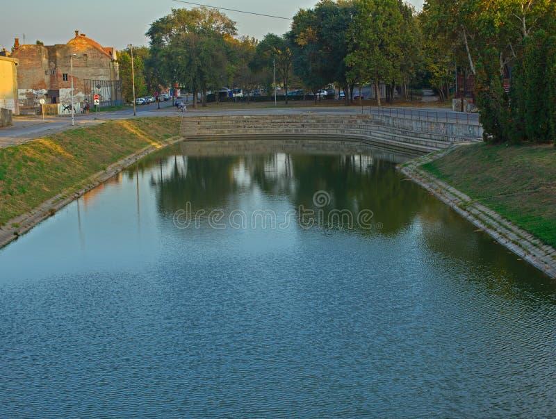 ZRENJANIN, SERBIA, il 14 ottobre 2018 - sponda del fiume con un bacino concreto fotografia stock