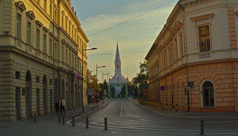 ZRENJANIN, SERBIA, il 14 ottobre 2018 - via che conduce alla chiesa cattolica immagine stock libera da diritti