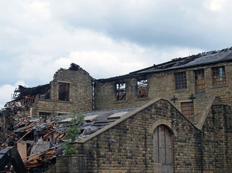 Zrujnowany przemysł zniszczony przez ogień z zapadającymi się ścianami i dachem oraz palone drewno zdjęcie royalty free
