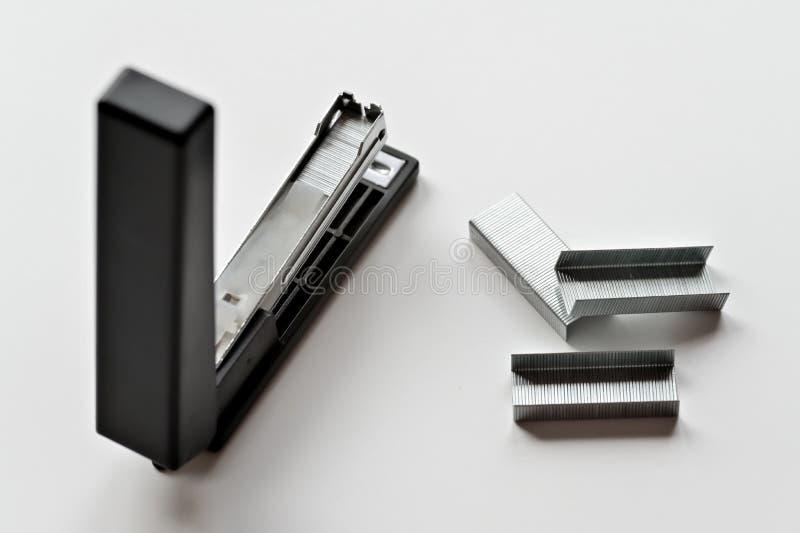 Zszywacza czerń z papierowymi klamerkami odizolowywać na białym tle obrazy stock