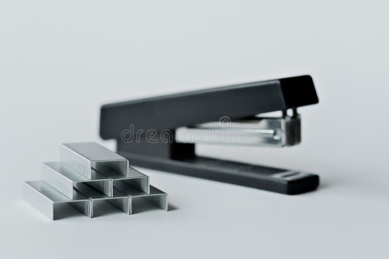 Zszywacza czerń z papierowymi klamerkami odizolowywać na białym tle fotografia royalty free