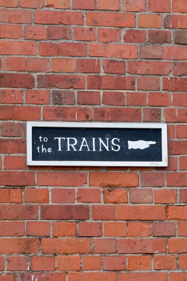 Zu den Zügen unterzeichnen Sie auf Wand Bahnhof lizenzfreie stockfotografie