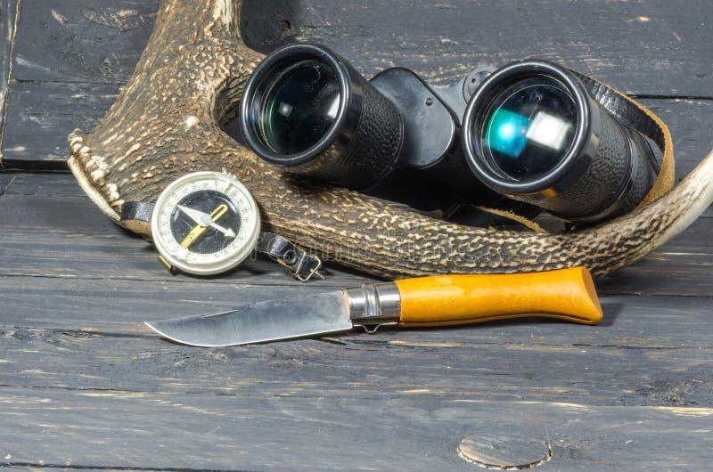 Zubehör für die Jagd Ferngläser, ein Messer und ein Kompass liegen nahe dem Geweih lizenzfreies stockbild