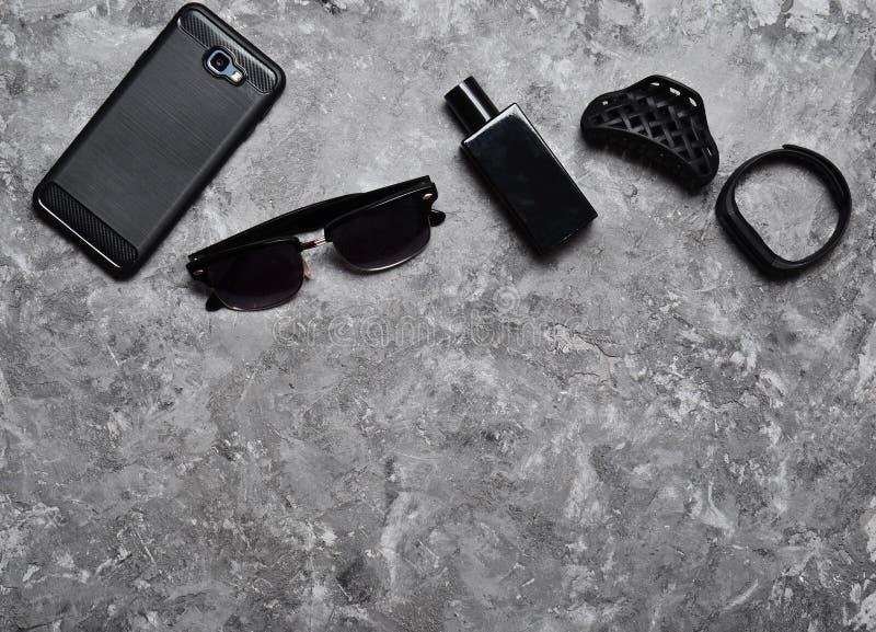 Zubehör für eine Geschäftsfrau auf einer konkreten Tabelle Geldbeutel, Parfüm, Sonnenbrille, intelligente Uhr, Smartphone, Stift  lizenzfreies stockbild