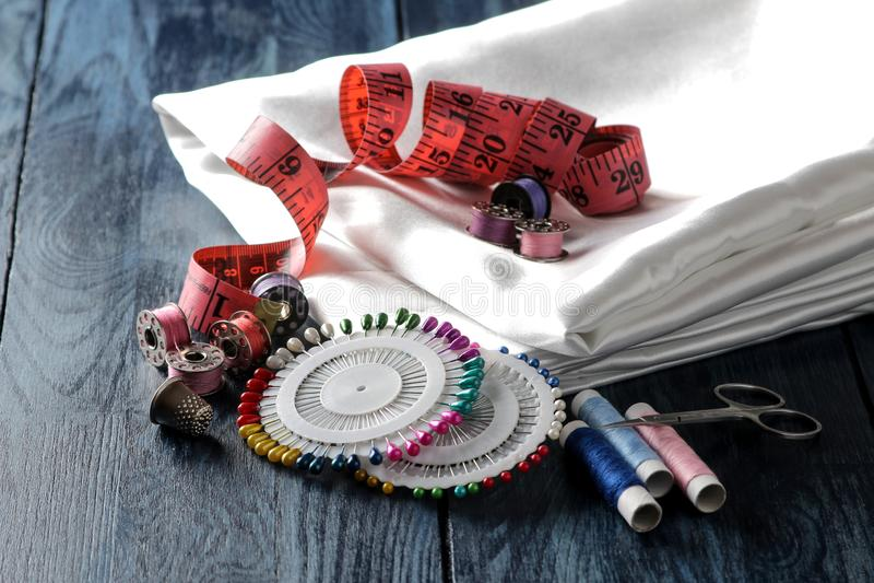 Zubehör für Nähen und Näharbeitthread, Gewebe, Scheren, Spulen, Stifte, Zentimeter auf einem blauen hölzernen Hintergrund stockbilder