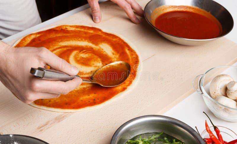 Zubereitung der Pizza Ausgebreitete Tomatensauce des Chefs in der Pizzeria lizenzfreie stockbilder