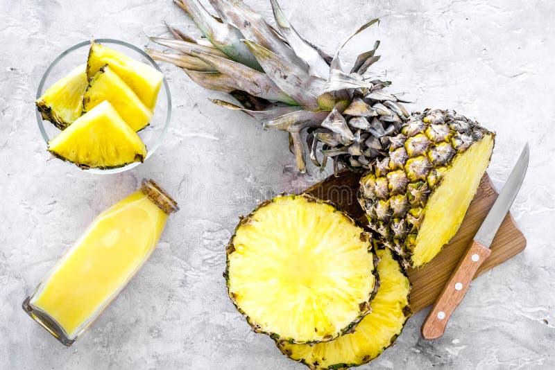 Zubereitung des Ananassafts Flasche mit Getränk nahe Fruchtscheiben und Messer auf Draufsicht des grauen Hintergrundes lizenzfreies stockbild