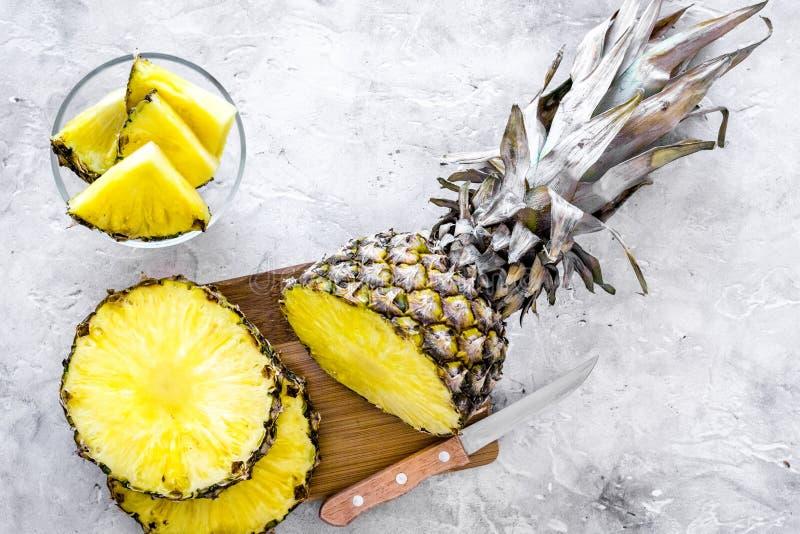 Zubereitung des Ananassafts Flasche mit Getränk nahe Fruchtscheiben und Messer auf Draufsicht des grauen Hintergrundes stockbild