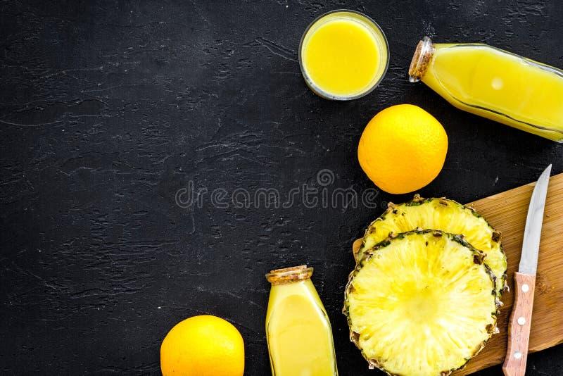 Zubereitung des Ananassafts Flasche mit Getränk nahe Fruchtscheiben und Messer auf schwarzem copyspace Draufsicht des Hintergrund lizenzfreies stockfoto