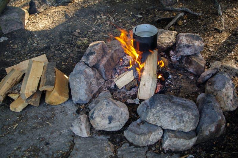 Zubereitung des Lebensmittels auf Lagerfeuer in einem Topf, wildes Kampieren lizenzfreie stockfotos